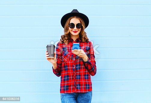 istock Fashion young woman with coffee cup resting using smartphone outdoors in city, wearing a black hat red checkered shirt 641006316