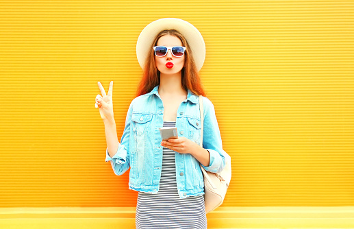 Fashion young woman with red lips is using smartphone in the city on orange background