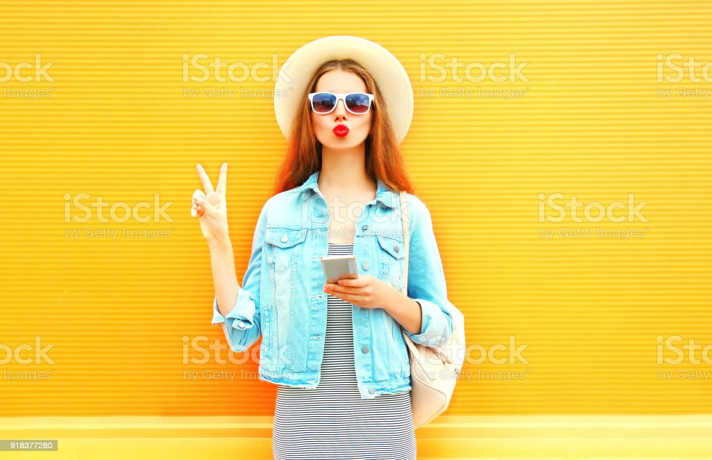 Fashion young woman with red lips is using smartphone in the city on orange background stock photo