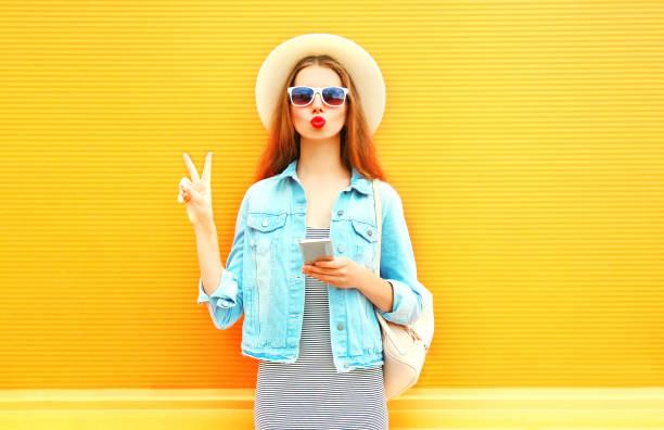 fashion junge frau mit roten lippen nutzt smartphone in der stadt auf orangem hintergrund - sommer teenagermode stock-fotos und bilder
