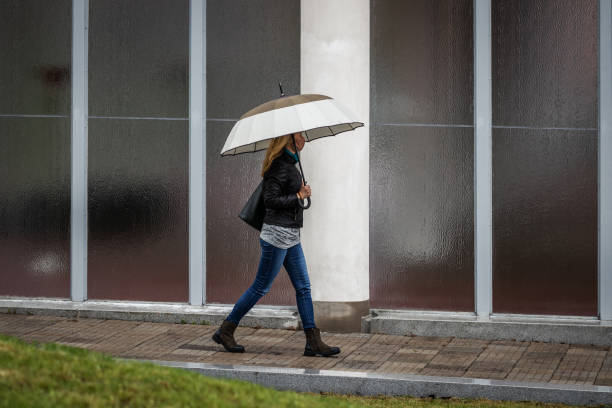 Fashionabla woman wearing face mask and walking with umbrella in rain stock photo