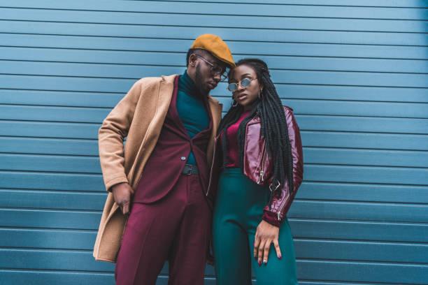 modieuze afrikaanse amerikaanse echtpaar in jas en overjas poseren samen buiten - street style stockfoto's en -beelden