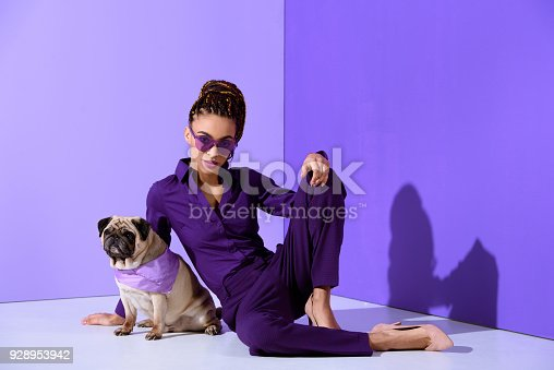 istock fashionable african american girl posing in purple suit with pug, ultra violet trend 928953942