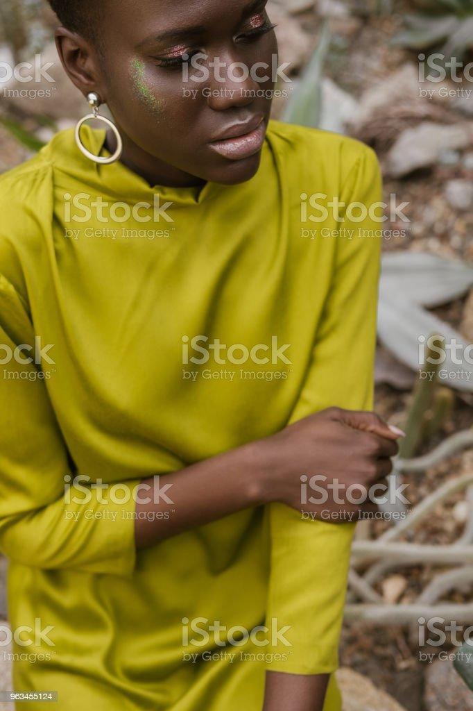la mode femme afro-américaine avec maquillage paillettes qui pose en robe jaune - Photo de A la mode libre de droits
