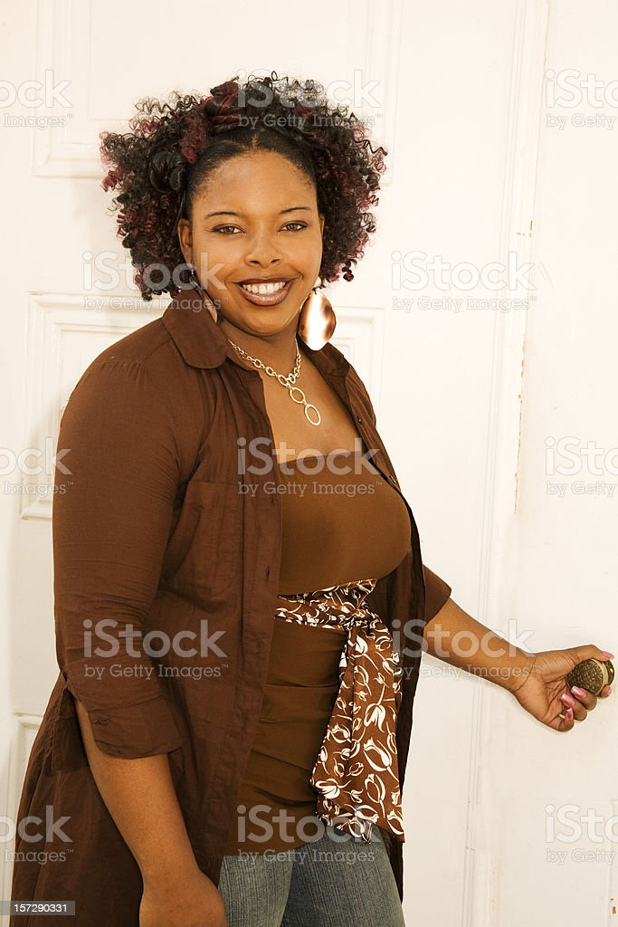 Fashionable African descent woman opening door. royalty-free stock photo