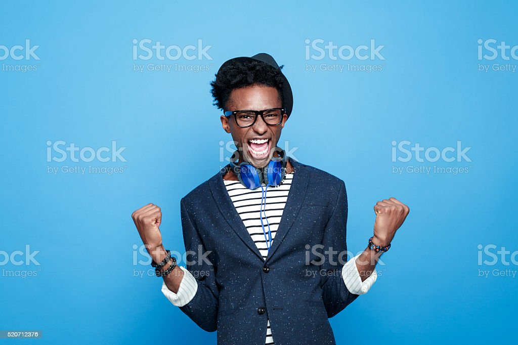 Fashionable afro american guy expressing happiness Studio portrait of successful afro american young man wearing striped top, navy blue jacket, nerd glasses, hat and headphone, laughing at camera with raised fists. Studio portrait, blue background. Adult Stock Photo