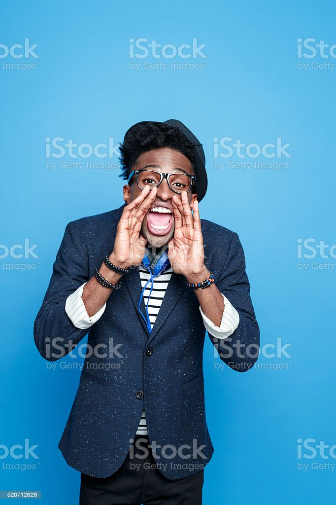 Fashionable afro american guy shouting at camera Studio portrait of funky afro american young man wearing striped top, navy blue jacket, nerd glasses, hat and headphone, shouting at camera. Studio portrait, blue background. Adult Stock Photo