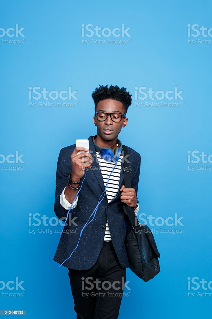 Fashionable afro american guy using a smart phone Studio portrait of fashionable afro american young man wearing striped top, navy blue jacket, nerd glasses and headphone, using a smart phone. Studio portrait, blue background. Adult Stock Photo