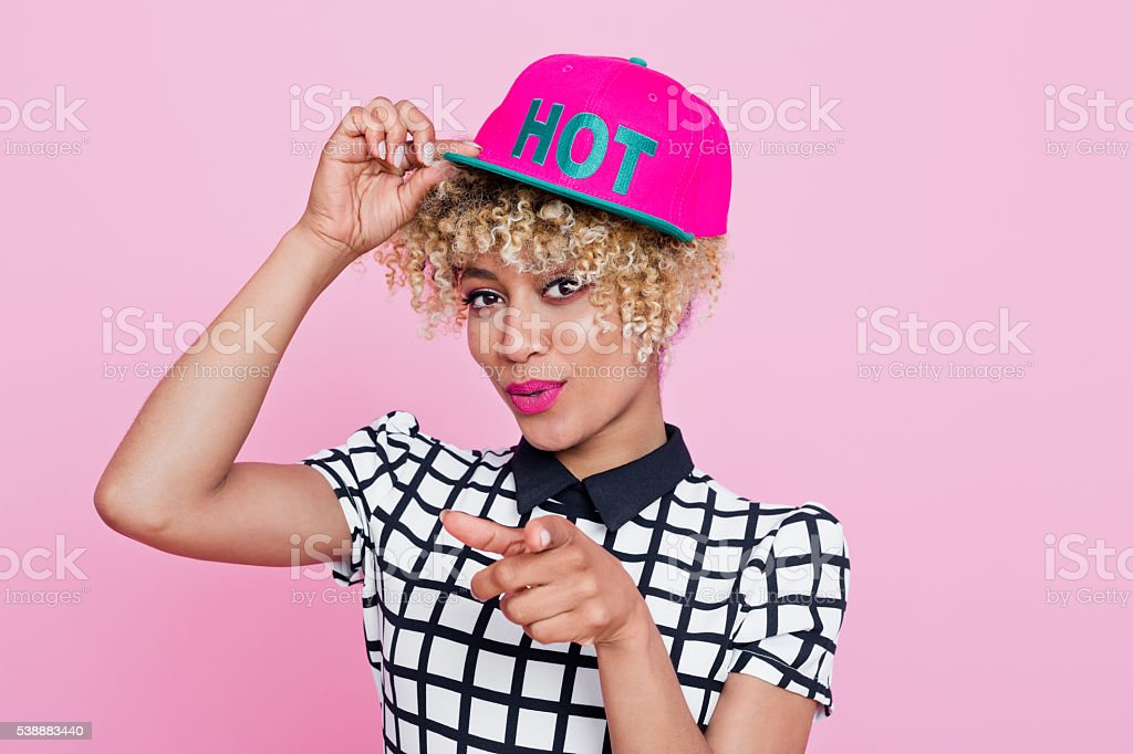 Fashionable afro american woman pointing with index finger Summer portrait of happy, afro american young woman wearing grid check playsuit and pink hat, standing against pink background and pointing her index finger at you. 25-29 Years Stock Photo
