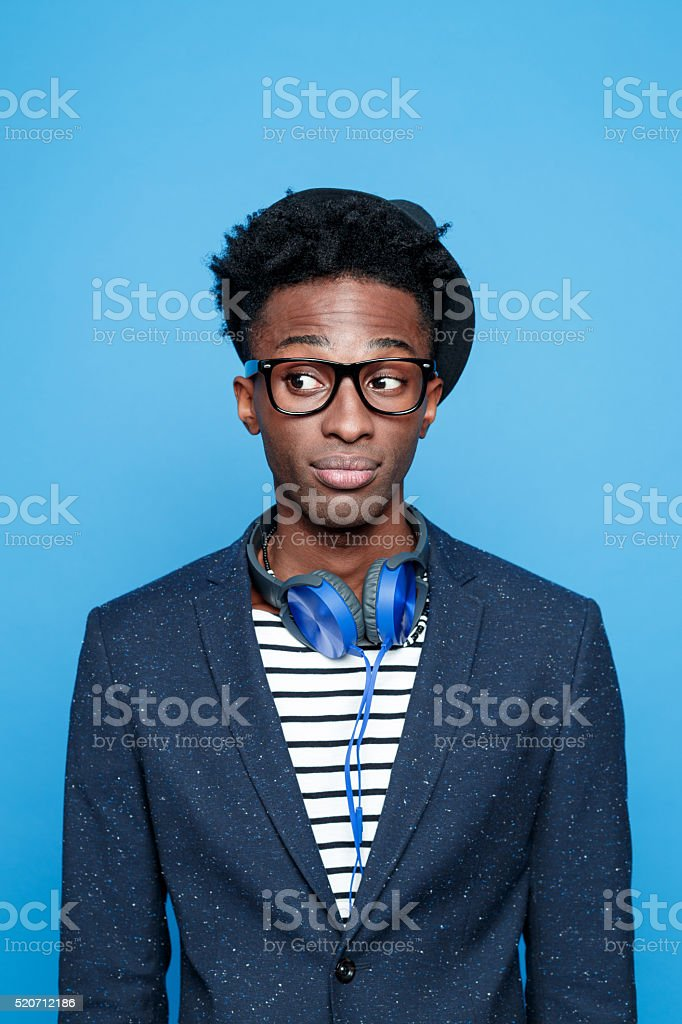 Fashionable afro american young man against blue background Studio portrait of pensive afro american young man wearing striped top, navy blue jacket, nerd glasses, hat and headphone, looking away. Studio portrait, blue background. Adult Stock Photo