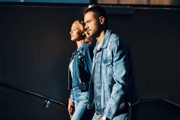 Modisches und selbstbewusstes junges Paar in Jeans gehen nach oben in Richtung Sonne – Foto