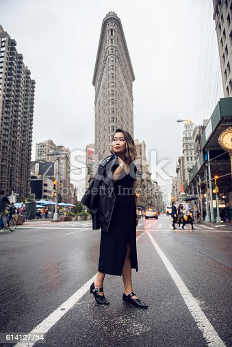 istock Fashionable asian woman crossing New York City street 614127754
