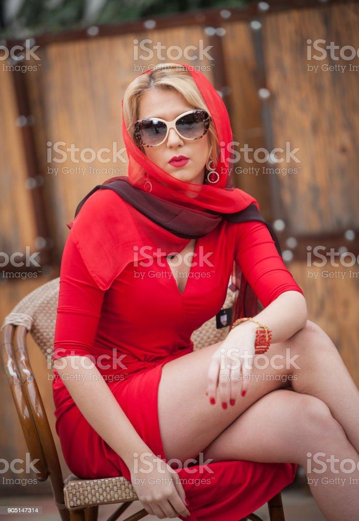 Modisch attraktive blonde Frau im roten Kleid auf Stuhl sitzend. – Foto