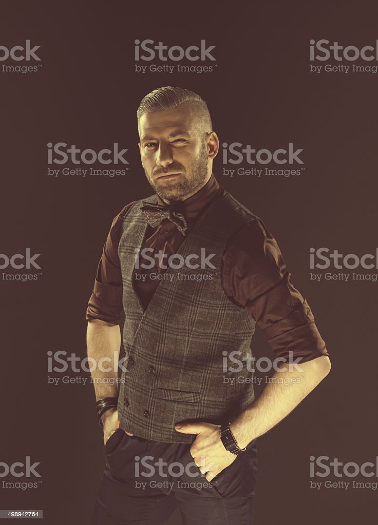 Fashionable bearded man wearing bow tie and tweed vest Handsome elegant man wearing tweed vest, shirt and bow tie, looking at camera. Dark tone, black background. 2015 Stock Photo