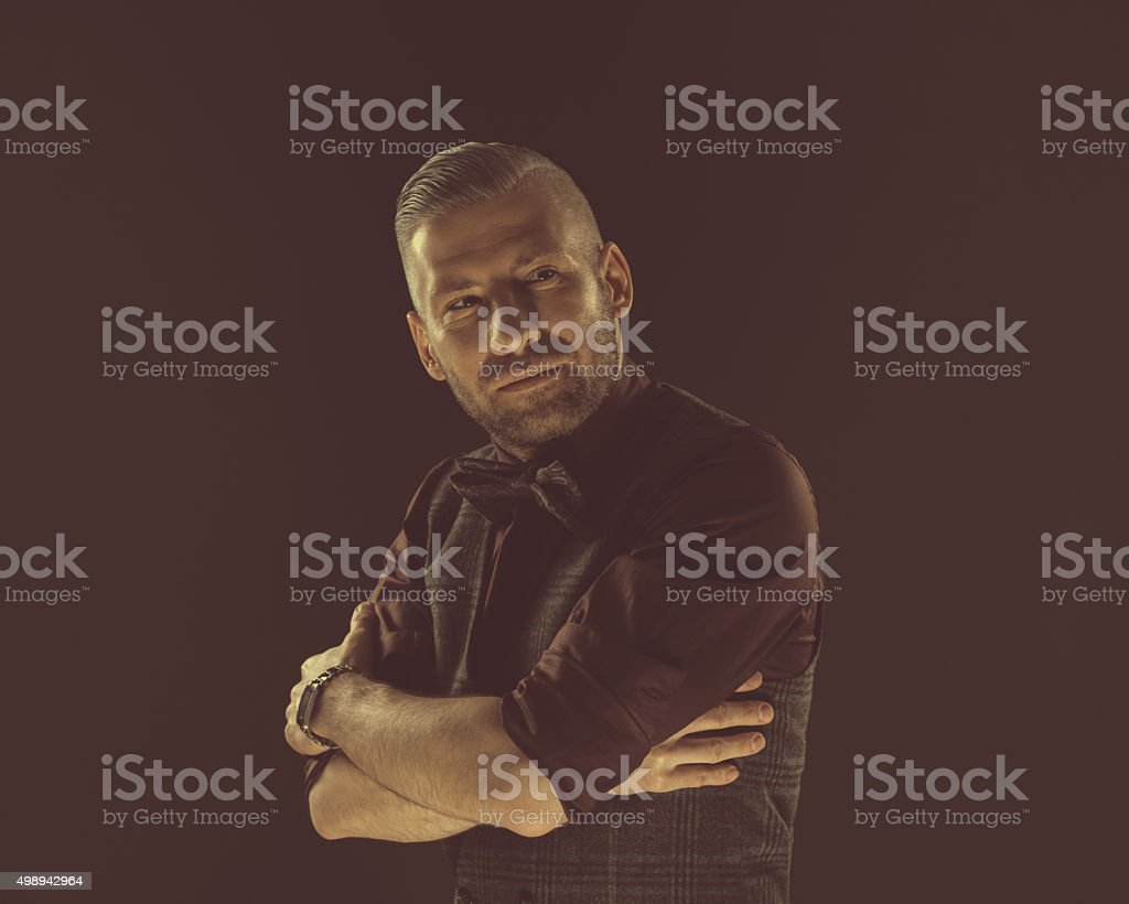 Fashionable bearded man wearing bow tie and tweed vest Handsome elegant man wearing tweed vest, shirt and bow tie. Dark tone, black background. 2015 Stock Photo