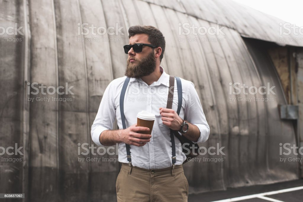 fashionable bearded man with sunglasses and leather backpack holding disposable coffee cup stock photo