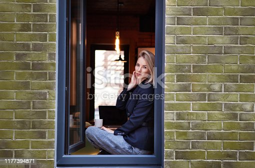 Fashionable beautiful businesswoman sitting in the window of the modern loft office. The model wears Stylish business clothes, black jacket, pants, accessories
