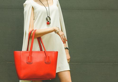 istock Fashionable beautiful red handbag on the arm of the girl 613655394
