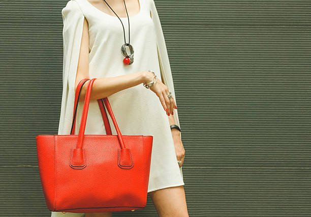 Fashionable beautiful red handbag on the arm of the girl stock photo