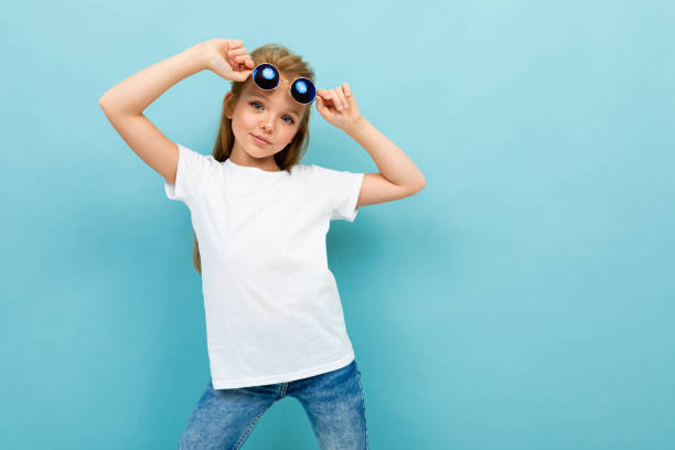 fashionable beautiful schoolgirl in a white shirt on a blue background posing stock photo