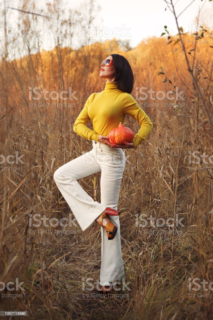 Fashionable beautiful woman in sunglasses standing in the field and holding a pumpkin for Halloween stock photo