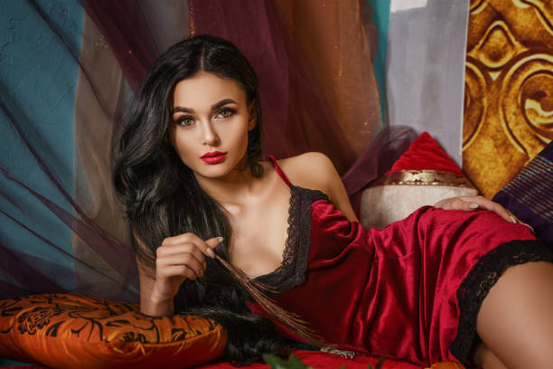 fashionable beautiful woman lies in a red negligee stock photo