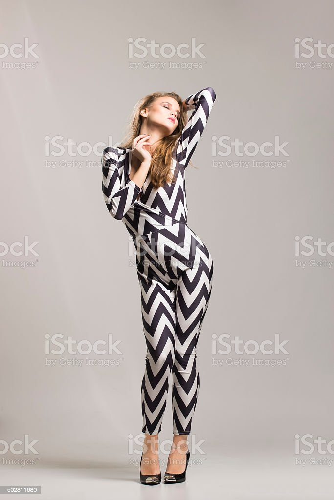 Fashionable beautiful young girl in 20s, posing. Studio shot, si stock photo
