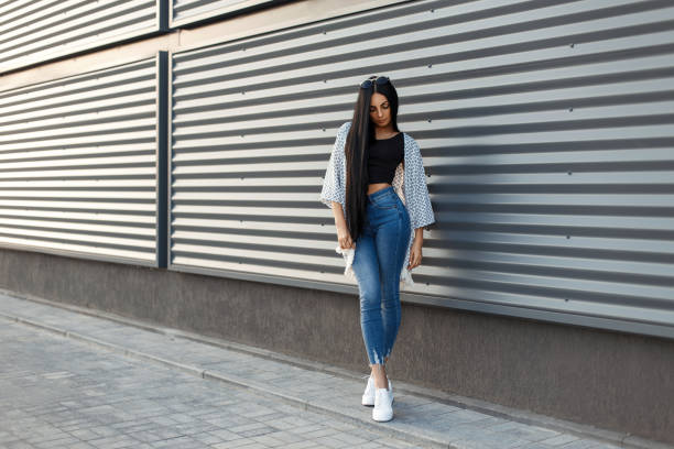 modische schöne junge frau mit langen schwarzen haaren in einen stilvollen weißen umhang mit klassischen jeans und weiße schuhe in der nähe einer modernen mauer mit linien - vogue muster stock-fotos und bilder