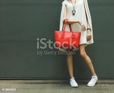 istock Fashionable big red handbag on the arm of the girl 613654620