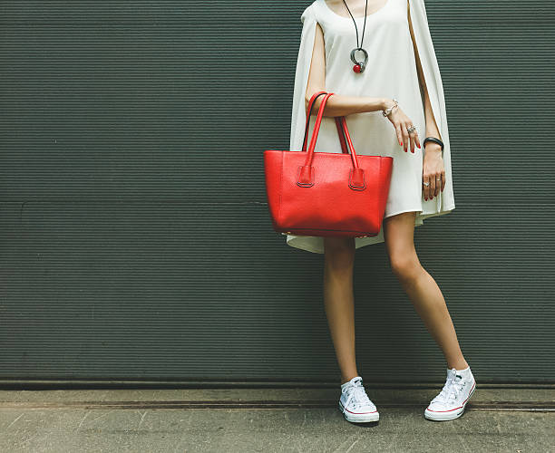 Fashionable big red handbag on the arm of the girl stock photo