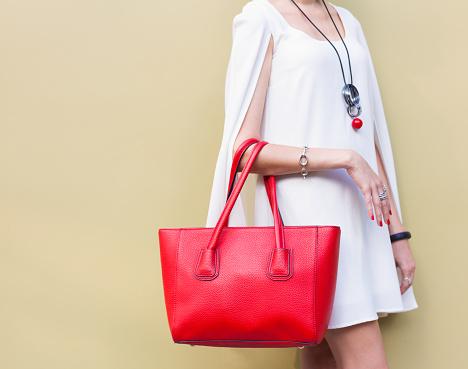 istock Fashionable big red handbag on the arm of the girl 613655846