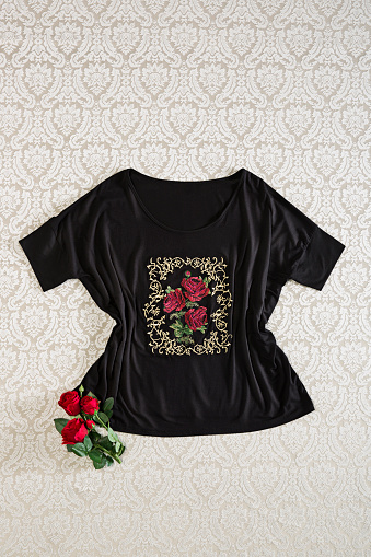 Fashionable black blouse with red roses isolated on wallpaper background
