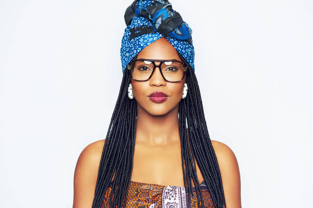 Fashionable black woman in ethnic clothes Head and shoulders portrait of fashionable young black woman in ethnic clothes with blue headscarf headscarf stock pictures, royalty-free photos & images