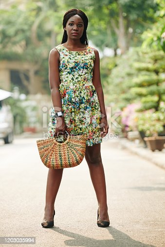 Stylish young Black woman wearing beautiful summer dress standing outdoors holding straw bag looking at camera, full shot