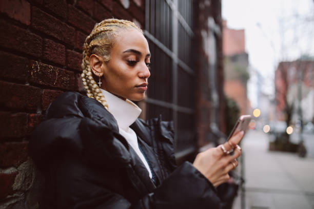 Fashionable blond woman texting on her phone in Lower Manhattan, New York stock photo