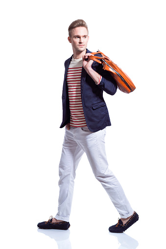 Portrait of fashionable blonde young man wearing navy blue jacket, striped blouse, white trausers and nerd glasses, holding leather bag. Studio shot, white background.