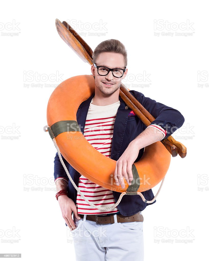 Fashionable blonde young man holding oars and lifebuoy stock photo