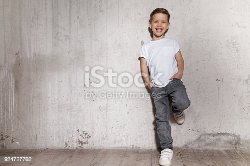 istock Fashionable boy posing in front of gray concrete wall. 924727762