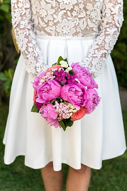 fashionable bride & wedding bouquet - mini dress stock photos and pictures