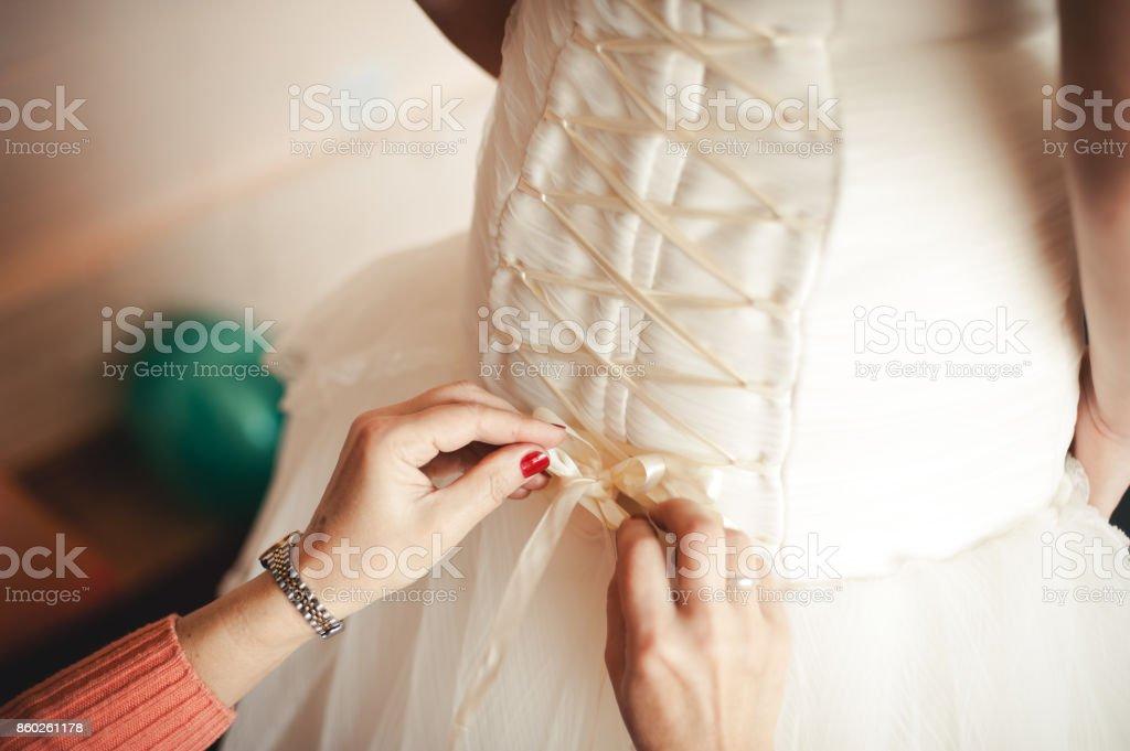 911b7783edbc Fashionable bridesmaids dresses helped wear bow on back of wedding dress  bride. Morning wedding day. - Stock image .
