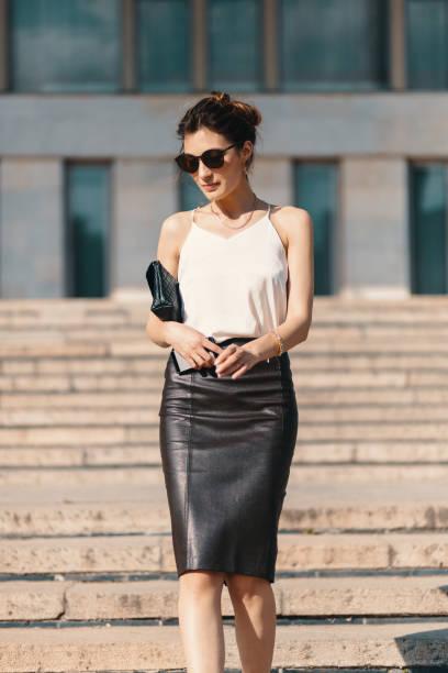 fashionable brunette businesswoman in leather pencil skirt and sunglasses walking in the street, on stairs - spódnica zdjęcia i obrazy z banku zdjęć
