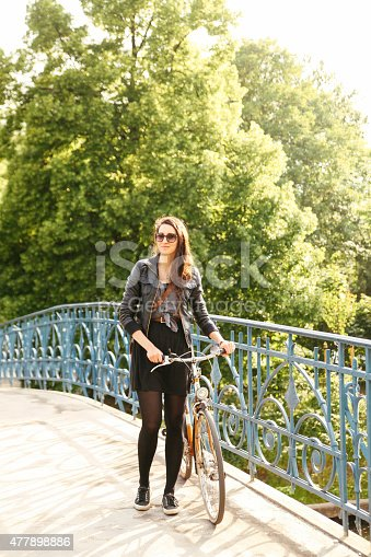 969439086 istock photo Fashionable brunette with a bicycle in the city 477898886
