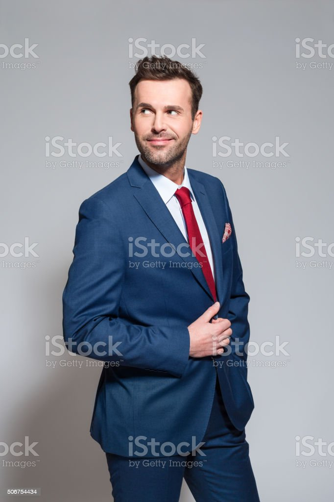Fashionable businessman wearing elegant suit Portrait of elegant businessman wearing elegant suit. Studio shot, one person, grey background. Adult Stock Photo