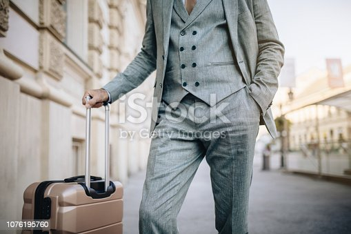 Fashionable senior businessman in suit, going through the city on a business travel, bringing his suitcase with him.