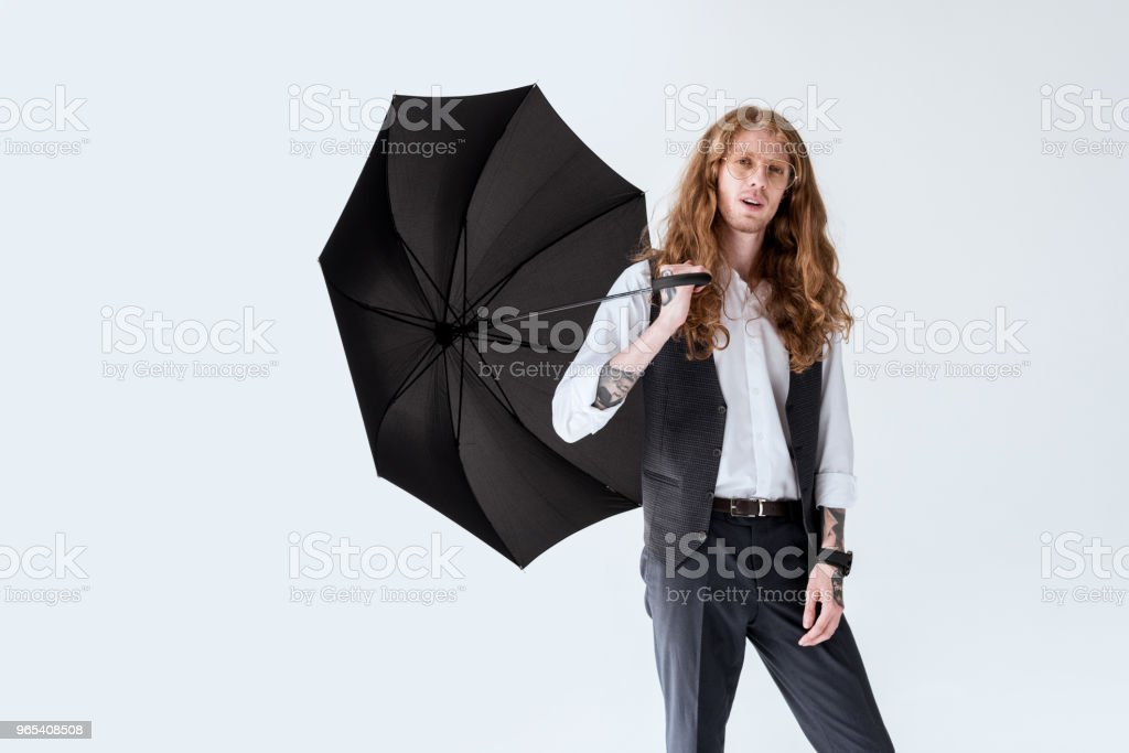 fashionable businessman with ginger hair holding black umbrella isolated on white zbiór zdjęć royalty-free