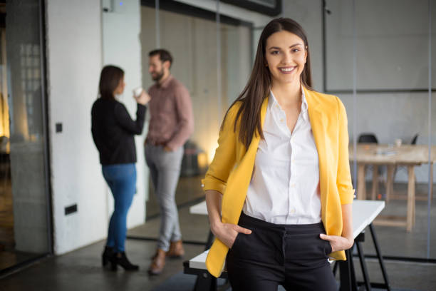 Fashionable businesswoman standing and looking at camera stock photo