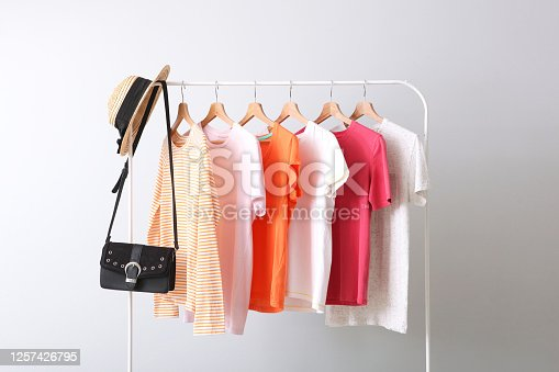 fashionable clothes on a rack in the interior of a bright room