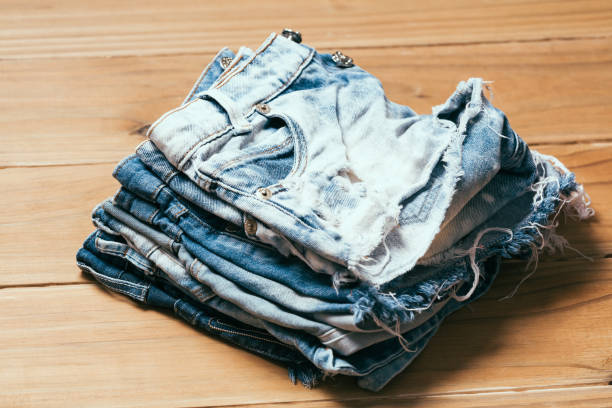 fashionable clothes. pile of jeans on a wooden background - jean shorts stock photos and pictures