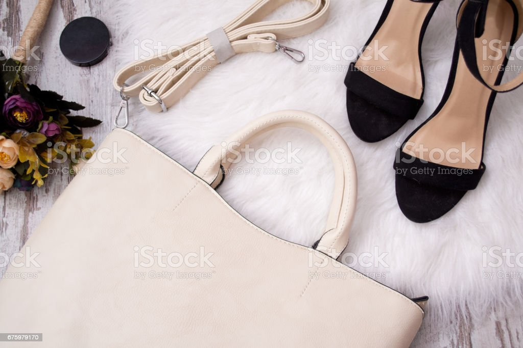 Fashionable concept. Light bag, black shoes and flowers on a white background. Top view stock photo
