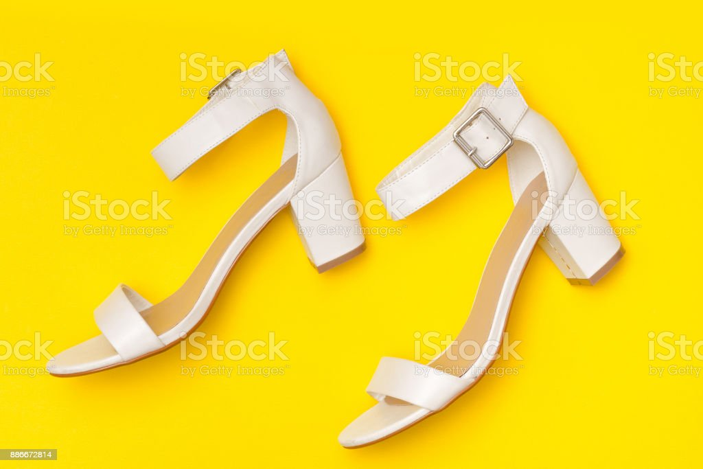 Fashionable concept. White shoes on yellow background, top view stock photo